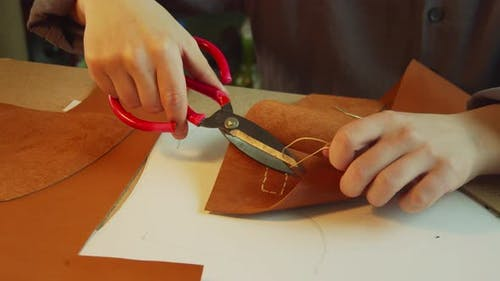 An Experienced Tanner in the Process of Creating a Women's Handbag. Cuts Off the Excess Sartorial