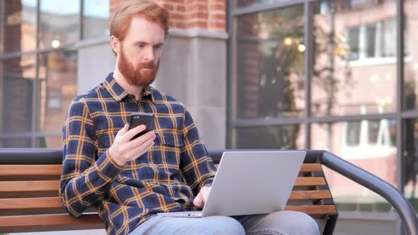 Thumbnail for Redhead Beard Young Man Using Smartphone and Laptop, Sitting on Bench