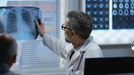 Male Doctor Showing X Ray To Patient