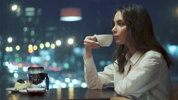 Thumbnail for Girl Pours Tea From the Kettle and Drinks It While Sitting in a Cafe.