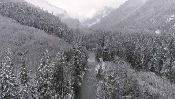 Thumbnail for Aerial Of Frozen Winter Landscape In Mountain Forest Valley With Snow Flakes Falling On Cold River