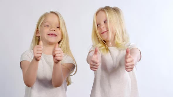 Thumbnail for Bubbly Caucasian Twins Showing Thumbs Up