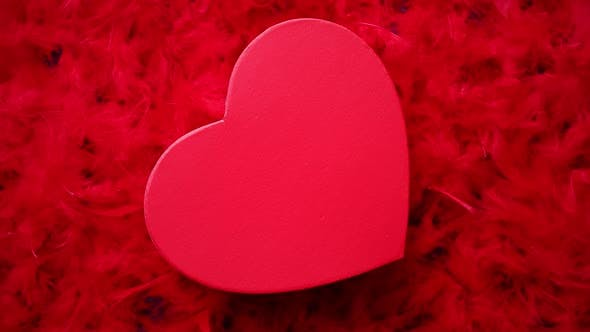 Thumbnail for Heart Shaped Boxed Gift, Placed on Red Feathers Background