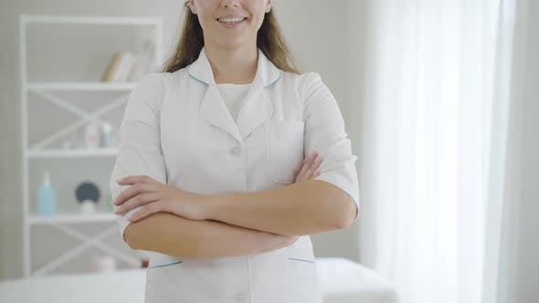Thumbnail for Unrecognizable Young Female Doctor Crossing Hands and Smiling. Confident Brunette Caucasian Woman