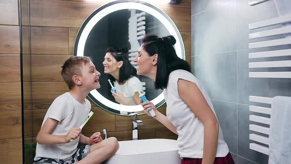 Thumbnail for Woman and Boy which Showing Each Other Their Teeth During Cleaning Them with Toothbrush