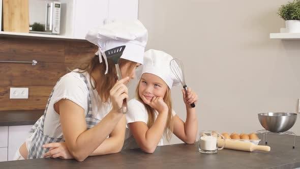 Porträt einer jungen kaukasischen Familie, die in Schürzen in der Küche steht und darüber nachdenkt, was zu backen ist