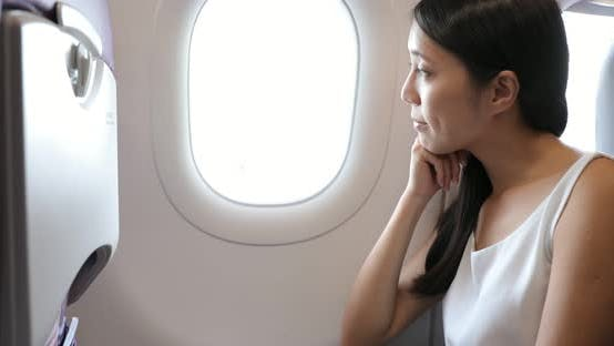 Thumbnail for Woman look out of window on airplane