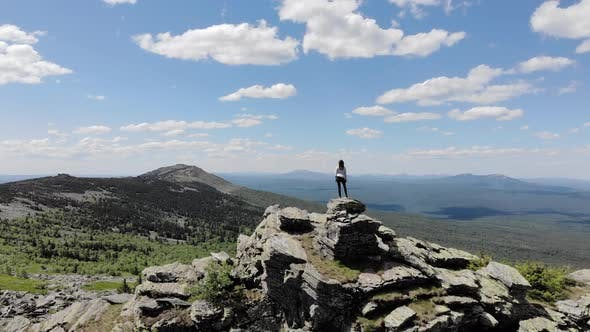 Thumbnail for Camera Follows Hipster Millennial Young Woman on Top of Mountain Summit
