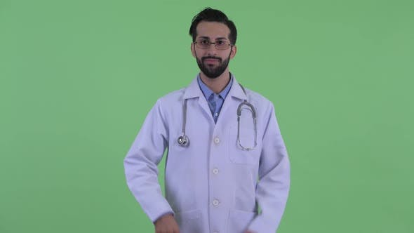 Thumbnail for Happy Young Bearded Persian Man Doctor Giving Thumbs Up and Looking Excited