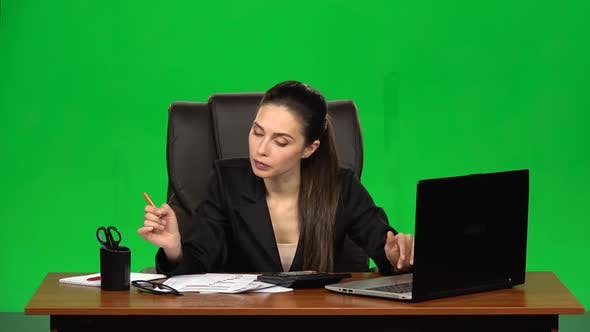 Business Woman in the Workplace Is Engaged in Finances, Makes Calculations on a Calculator and Fills