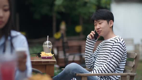 Thumbnail for Asian Boy Having Phone Conversation in Outdoor Restaurant