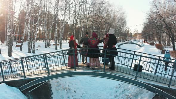 Russian Folklore - People in Russian Costumes Are Dancing on the Bridge