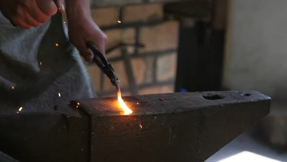 Thumbnail for Blacksmith Hitting a Molten Iron Rose with a Hammer on an Anvil in an Old Forge
