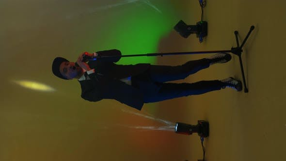Vertical Video. A Funny Man Sings and Dances Into a Microphone on a Stand in the Neon Light of Lamps