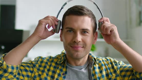 Thumbnail for Portrait of Young Happy Man Putting Wireless Headset on