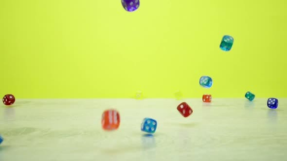 Thumbnail for Slow-mo Shot of Multicolored Dice Fall on a Yellowbackground