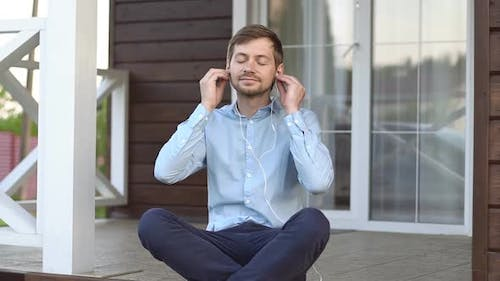 Young man sitting on terrace, listens relaxing music through headphones and meditating
