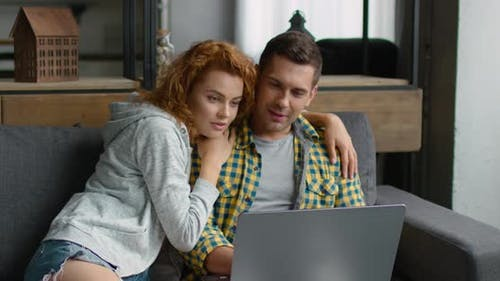 Young Man and Woman Are Watching Video on Their Laptop