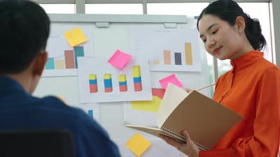 Young Woman Explains Business Data on White Board