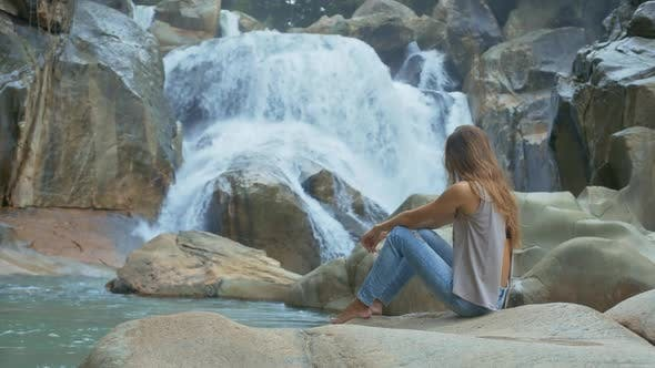 Thumbnail for Barefoot Girl Sits and Looks at Waterfall on Rocks