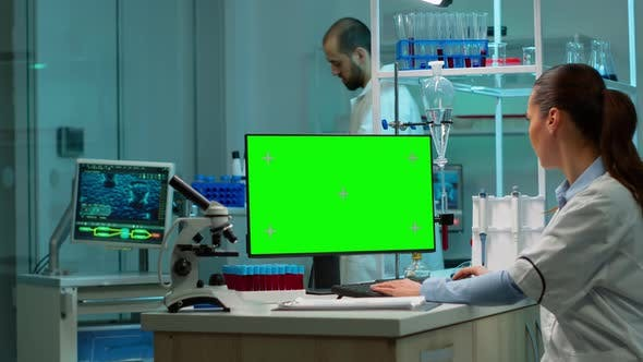 Thumbnail for Biochemist Sitting at Workplace Using Green Mockup Screen Pc