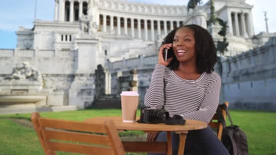 Thumbnail for Smiling black woman sits at table outside Piazza Venezia chatting on phone