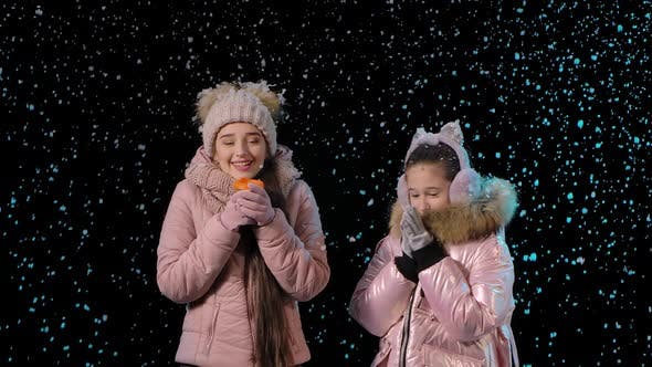 The Frozen Mother and Daughter Keep Warm with a Hot Drink. A Woman and a Little Girl Rejoice in the