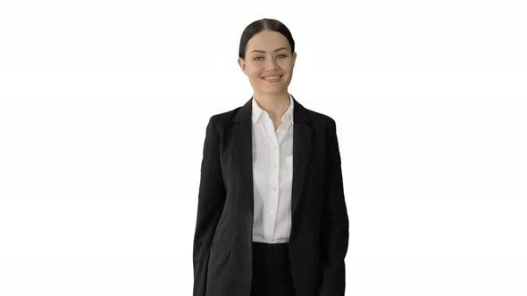 Confident Businesswoman Walking Towards Looking at Camera with a Smile on White Background.