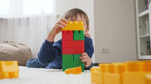 Little Boy Building High Tower From Colorful Plastic Toy Blocks