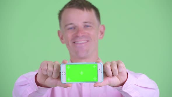 Cover Image for Face of Happy Businessman Showing Phone