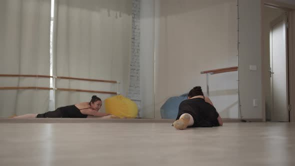 Ballerina Sits on the Splits in Front of the Mirror at a Rehearsal in the Hall and Pulls Her Back