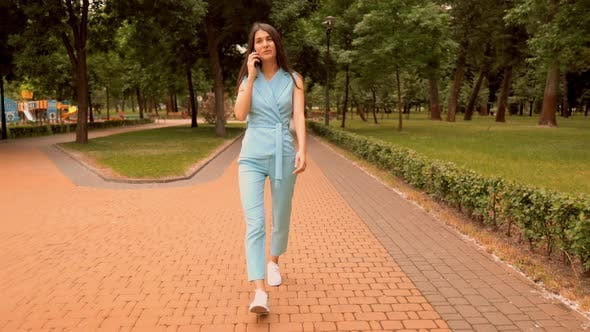 Thumbnail for Young Caucasian Woman Speaking with Friend By Mobile Walking on the Street in City Park