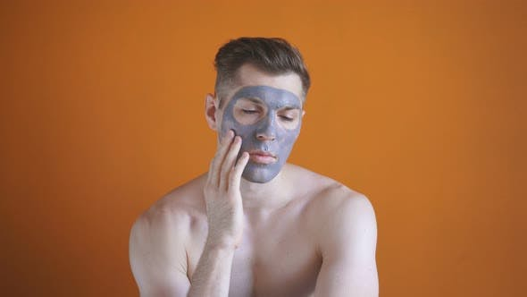 Beautiful Young Man Uses Clay Face Mask, Skin Care, Isolated Background