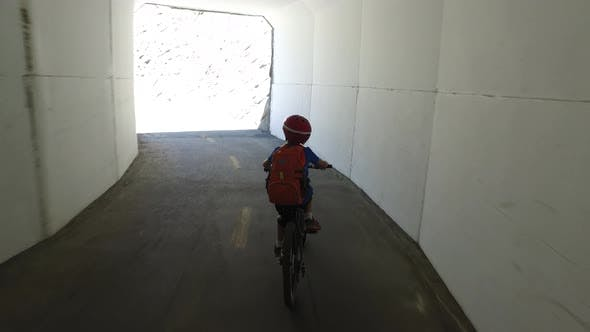 Thumbnail for A boy rides his mountain bike through a tunnel on a paved trail in the woods.