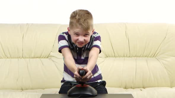 Thumbnail for Kid Plays with Joystick in Online Game Sitting on Couch