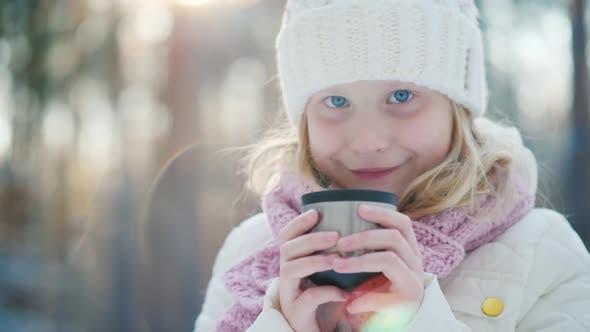 Thumbnail for Ein 6 Jahre altes Mädchen trinkt heißen Tee auf der Straße
