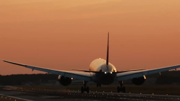 Thumbnail for Airplane is landing to the runway at sunset. Back view