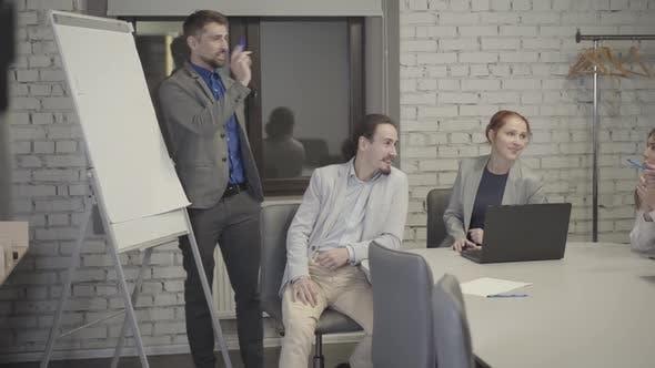 Thumbnail for Bärtiger Kaukasier im grauen Anzug stehend neben Bord im Open Space Office und im Gespräch mit