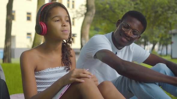 Thumbnail for Portrait of Cheerful Cute Girl Listening To Music in Headphones and Giving Earphones To Young