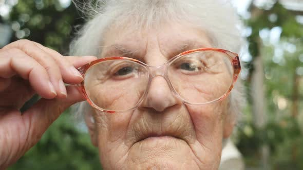 Old Woman Straightens Her Glasses and Looking at Camera