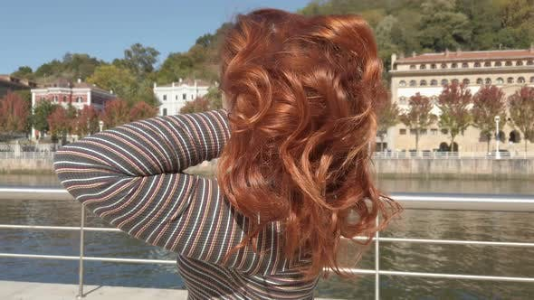 Young woman contemplating the views of the Bilbao city and the Nervion River stacked on the railing
