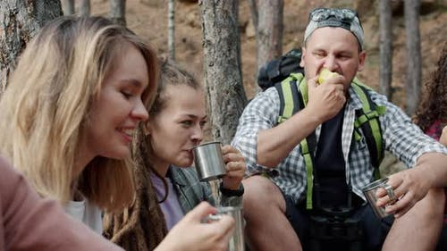 Group of Friends Tourists Drinking and Eating Relaxing in Forest on Autumn Day
