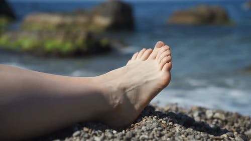 Female Legs on the Background of the Beach on the Sea of Pebbles. Rest and Relaxation, Slow Motion