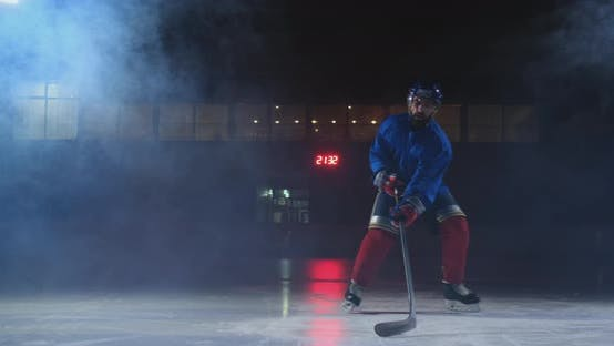 Thumbnail for Professional Hockey Player with a Stick and a Puck Moves on Luda in Skates and Helmet on a Dark