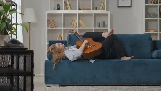 Grief of Love and Romantic Feelings of Young Woman Playing Guitar Lady Is Lying on Couch in