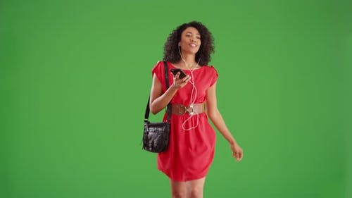 Happy woman walking and listening to smartphone streaming music on greenscreen