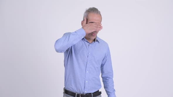 Thumbnail for Stressed Persian Businessman Covering Eyes Against White Background