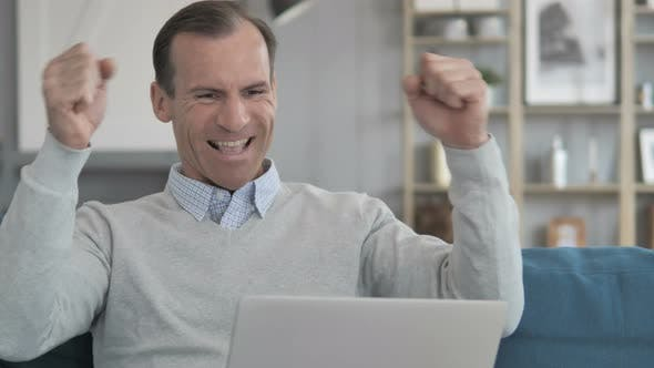 Thumbnail for Middle Aged Man Celebrating Success on Laptop  at Creative Office