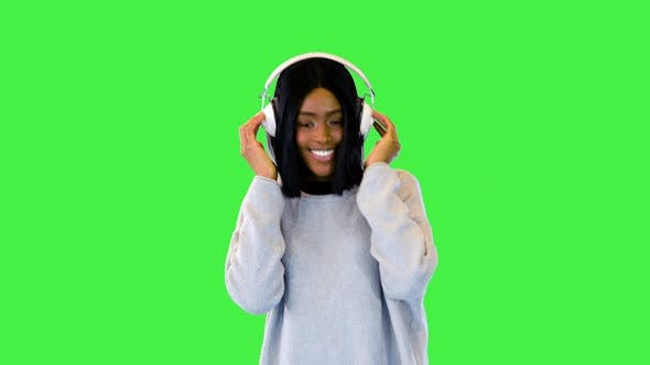 Beautiful African American Girl Enjoy Music Dance Wearing Modern Headphones and Happy Smiling on a