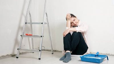 Depressed Lady Designer Holds Head on Hands in New Apartment
